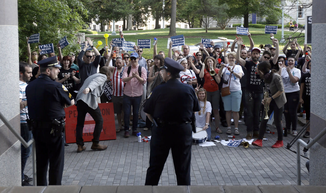 <p>Protesters gather outside the the North Carolina Museum of History as Gov. Pat McCrory speaks about House Bill 2 during a government affairs conference in Raleigh, N.C., on May 4, 2016. A North Carolina law limiting protections to LGBT people violates federal civil rights laws and can't be enforced, the U.S. Justice Department said on Wednesday, putting the state on notice that it is in danger of being sued and losing hundreds of millions of dollars in federal funding.<i> (Gerry Broome/AP)</i></p>