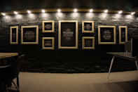 A collage of pinewood frames in blackboard theme on a brick wall in the black zone of the campus.