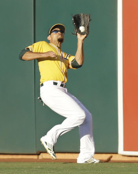 Oakland Athletics center fielder Coco Crisp catches a ball hit by Detroit Tigers Victor Martinez in the second inning of Game 5 of an AL baseball division series in Oakland, Calif., Thursday, Oct. 10, 2013. (AP Photo/Ben Margot)