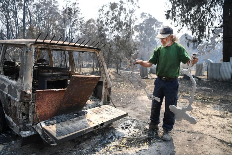 Thomas Eveans holds melted aluminium as he inspects the remains of his house which was destroyed by a bushfire in Torrington, near Glen Innes