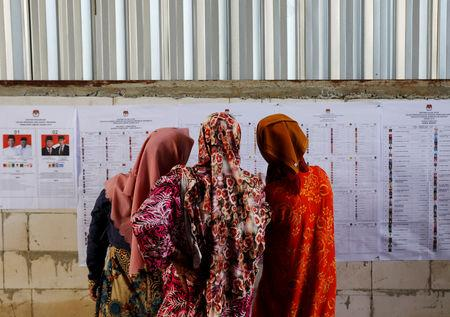 People look at voting information at a polling station during elections in Bogor, West Java, Indonesia April 17, 2019. REUTERS/Willy Kurniawan/Files