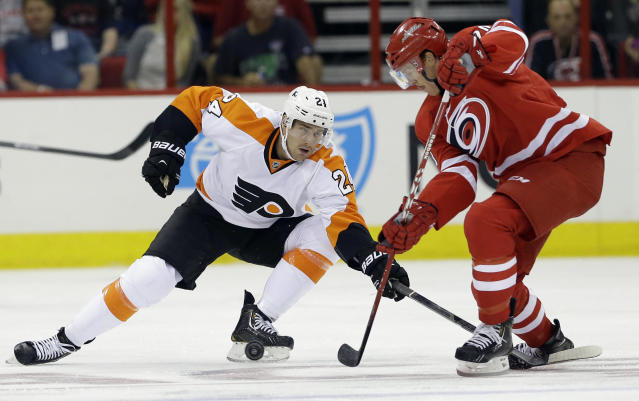 Philadelphia Flyers' Matt Read (24) reaches for the puck as Carolina Hurricanes' Riley Nash, right, looks for control during the first period of an NHL hockey game in Raleigh, N.C., Sunday, Oct. 6, 2013. (AP Photo/Gerry Broome)