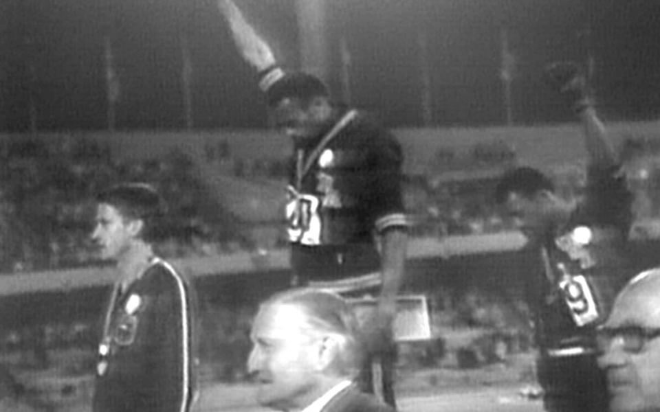 Gold medalist Tommie Smith and bronze medalist John Carlos showing raised fists on the podium after the 200m race at the 1968 Olympics - Sky History