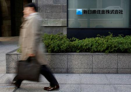 FILE PHOTO: A pedestrian walks past a logo of Nippon Steel & Sumitomo Metal Corp outside its headquarters in Tokyo February 7, 2014.   REUTERS/Yuya Shino/File Photo