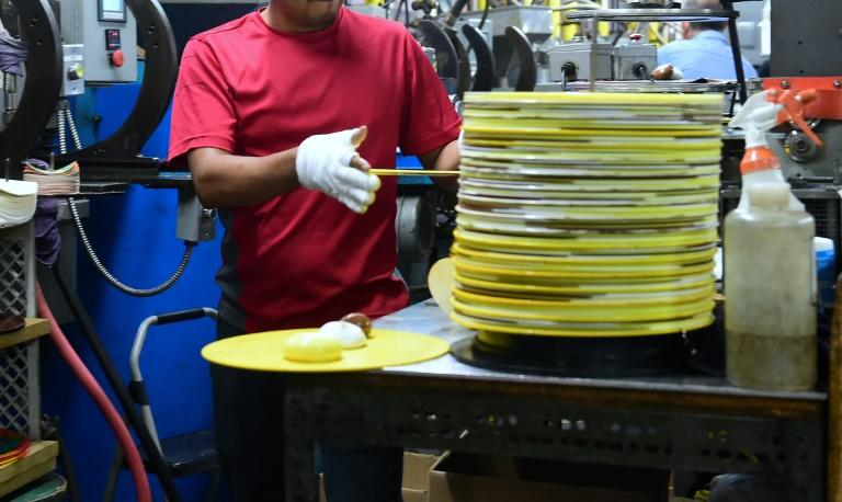 Employees at Erika Records work in the record pressing plant in Buena Park, California on April 12, 2017, where Erika Records has been pressing vinyl in its record manufacturing business for over 30 years