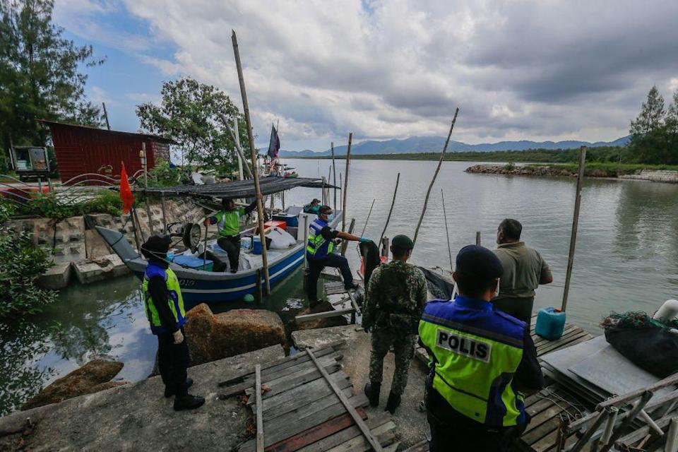 Police and Armed Forces personnel conduct checks on a fishing boat in Kampung Pulau Betong in Balik Pulau April 8, 2020. — Picture by Sayuti Zainudin