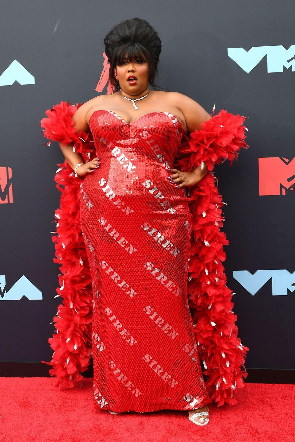 """<p>As the breakout star of the year, Lizzo's """"Siren"""" dress by Moschino was red-hot and entirely appropriate. The hair full of secrets and fabulous boa? The icing on the cake.</p>"""