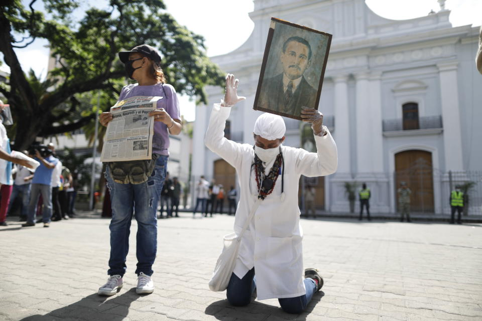 """Yeni Vasquez raises a portrait of the late, Venezuelan Dr. Jose Gregorio Hernandez outside the church in La Candelaria after the church bell rang, signaling the start of his Beatification ceremony in Caracas, Venezuela, Friday, April 30, 2021. Known as the """"doctor of the poor, Hernandez is being Beatified by the Catholic church, a step towards sainthood. (AP Photo/Ariana Cubillos)"""
