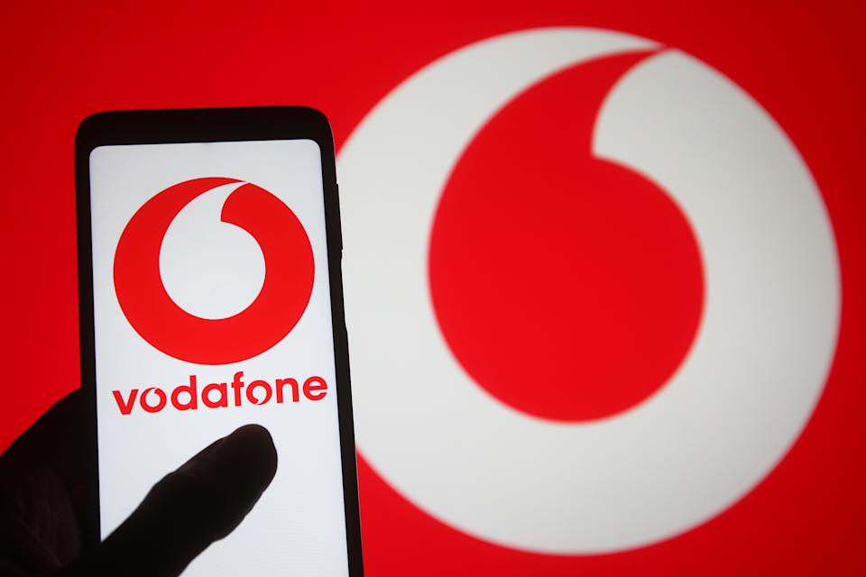 Vodafone logo of a multinational telecommunications company seen displayed on a smartphone into a silhouette of a hand. (Photo Illustration by Pavlo Gonchar/SOPA Images/LightRocket via Getty Images)