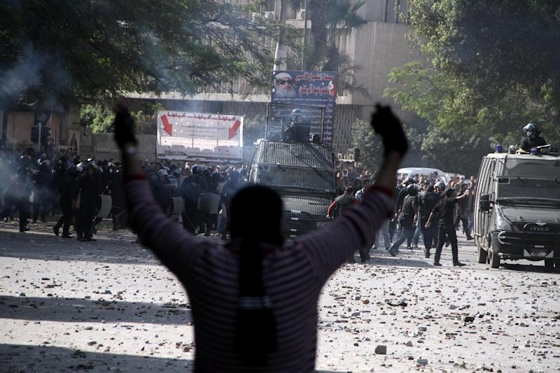 Egyptian security forces, background, clash with protesters near Tahrir Square in Cairo, Egypt, Sunday, Nov. 25, 2012. Supporters and opponents of Egypt's president grow more entrenched in their potentially destabilizing battle over the Islamist leader's move to give himself near absolute powers, with neither side appearing willing to back down. (AP Photo/Ahmed Gomaa)