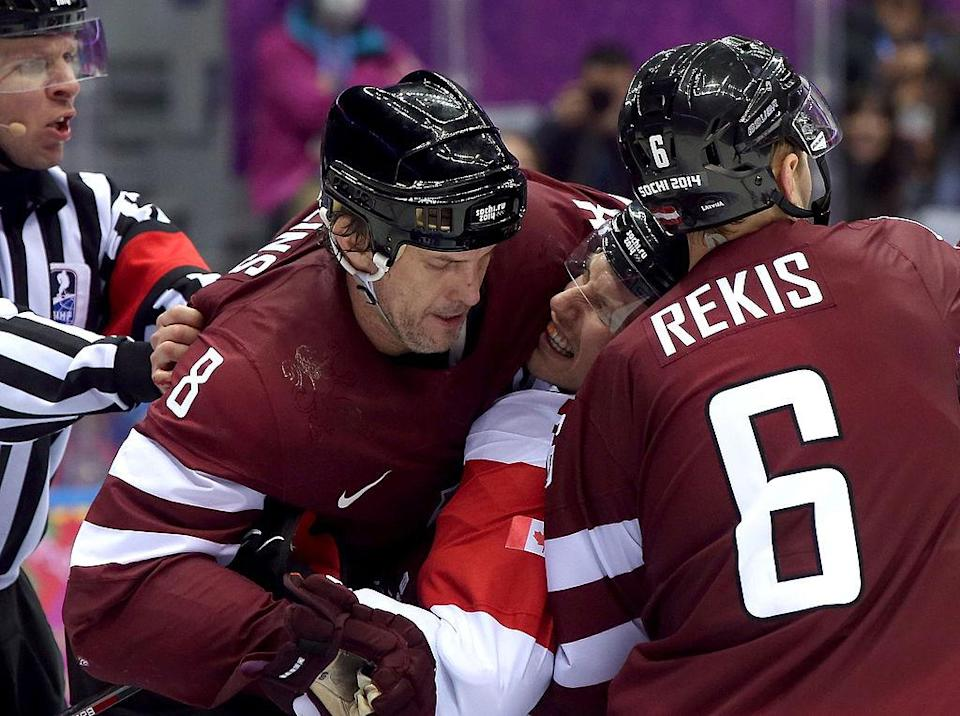 SOCHI, RUSSIA – FEBRUARY 19: Ryan Getzlaf #15 of Canada gets squeezed between Sandis Ozolins #8 and Arvids Rekis #6 of Latvia during the Men's Ice Hockey Quarterfinal Playoff on Day 12 of the 2014 Sochi Winter Olympics at Bolshoy Ice Dome on February 19, 2014 in Sochi, Russia. (Photo by Bruce Bennett/Getty Images)