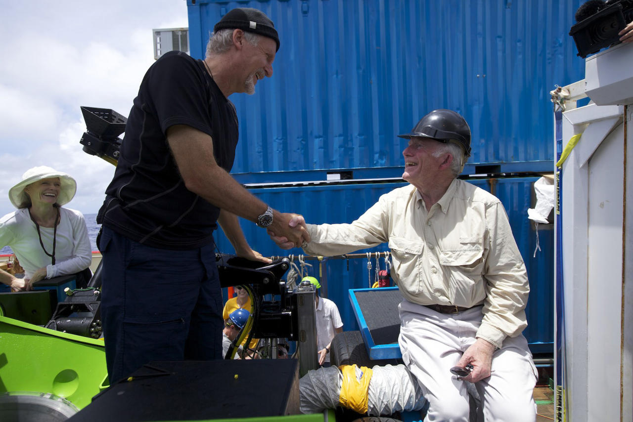 "Filmmaker and National Geographic Explorer-in-Residence James Cameron is congratulated by ocean explorer and U.S. Navy Capt. Don Walsh, right, after completing the first ever solo dive to the ""Challenger Deep,"" the lowest part of the Mariana Trench. Walsh took the same journey to the bottom of the Mariana Trench 52 years ago in the bathyscaphe Trieste with Swiss oceanographer Jacques Piccard. Cameron's dive in his specially designed submersible was part of Deepsea Challenge, a joint scientific expedition by Cameron, the National Geographic Society and Rolex to conduct deep-ocean research. (AP Photo/Mark Theissen, National Geographic)"