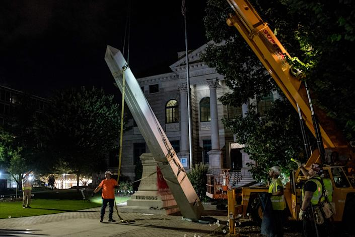 Hundreds of people cheered as crews worked to move the Confederate monument from Decatur Square on the eve of Juneteenth.