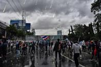 Thai police stationed on an elevated tollway deployed water cannon against protesters who set off firecrackers and threw projectiles