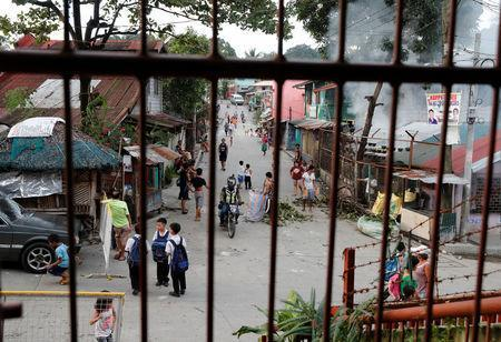 Residents are pictured along a street in Barangay Payatas district in Quezon City, Metro Manila in the Philippines December 11, 2017. REUTERS/Erik De Castro