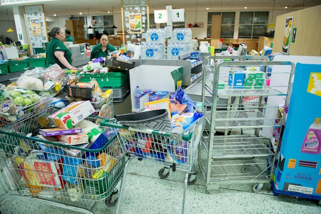 Workers collect items to restock the empty shelves in a London Morrisons store as panic-buying over coronavirus continues on 14 March 2020 in London. (Photo by Ollie Millington/Getty Images)