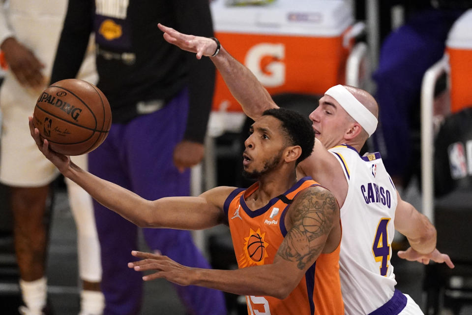 Phoenix Suns guard Cameron Payne, left, shoots as Los Angeles Lakers guard Alex Caruso defends during the first half in Game 4 of an NBA basketball first-round playoff series Sunday, May 30, 2021, in Los Angeles. (AP Photo/Mark J. Terrill)