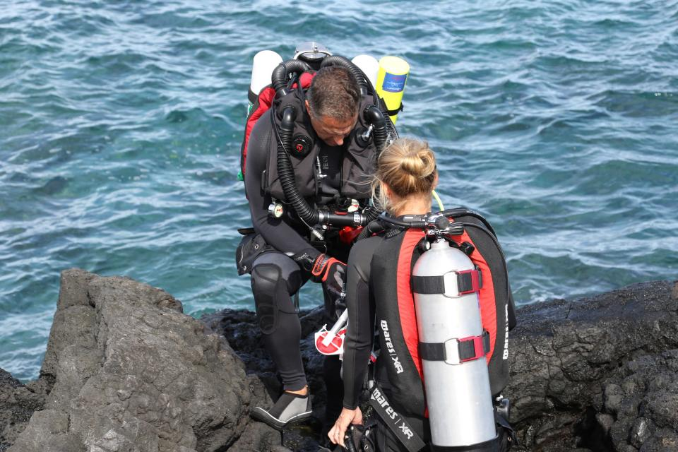 In this Sept. 13, 2019 photo, researchers prepare to dive on a coral reef on the west coast of the Big Island near Captain Cook, Hawaii. One of the state's most vibrant coral reefs thrives just below the surface in a bay on the west coast of Hawaii's Big Island. Here, on a remote shoreline far from the impacts of sunscreen and throngs of tourists, scientists see the early signs of what's expected to be a catastrophic season of coral bleaching in Hawaii. The ocean here is about three and a half degrees above normal for this time of year. Coral can recover from bleaching, but when it is exposed to heat over several years, the likelihood of survival decreases. (AP Photo/Caleb Jones)