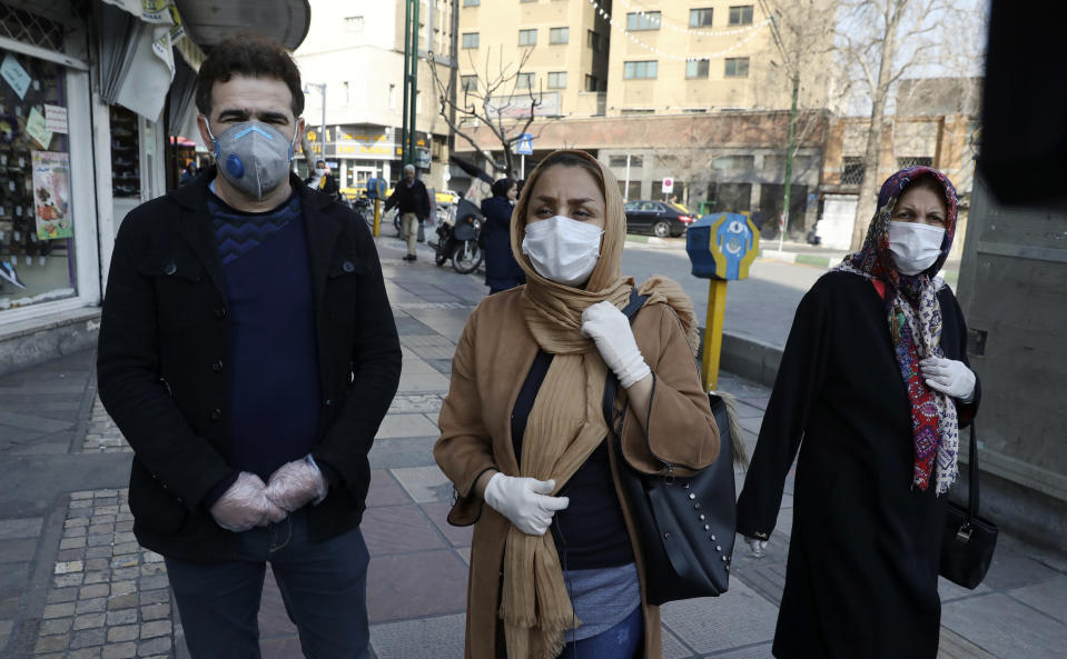 Tehran resident Leila Tayyeb, center, with her husband wearing mask and gloves, speaks with The Associated Press, as a woman walks past, in downtown Tehran, Iran, Thursday, Feb. 27, 2020. Amid fear and uncertainty caused by the spread of a new virus, Iranians are taking extra caution to avoid getting infected, as authorities canceled Friday prayers in Tehran, Qom and other cities. (AP Photo/Vahid Salemi)