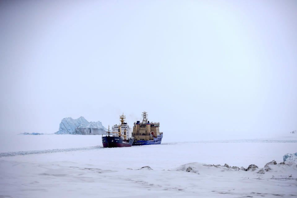 An Icebreaker making the path for a cargo ship with an iceberg in the background near a port on the Alexandra Land island near Nagurskoye, Russia, Monday, May 17, 2021. Once a desolate home mostly to polar bears, Russia's northernmost military outpost is bristling with missiles and radar and its extended runway can handle all types of aircraft, including nuclear-capable strategic bombers, projecting Moscow's power and influence across the Arctic amid intensifying international competition for the region's vast resources. (AP Photo/Alexander Zemlianichenko)
