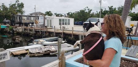 Terri Metter and her Boston Terrier Nikki overlook what's left of destroyed trailers that fill a canal near a trailer park in Marathon, Florida, U.S., June 10, 2018.  Picture taken June 10, 2018.  REUTERS/Zach Fagenson