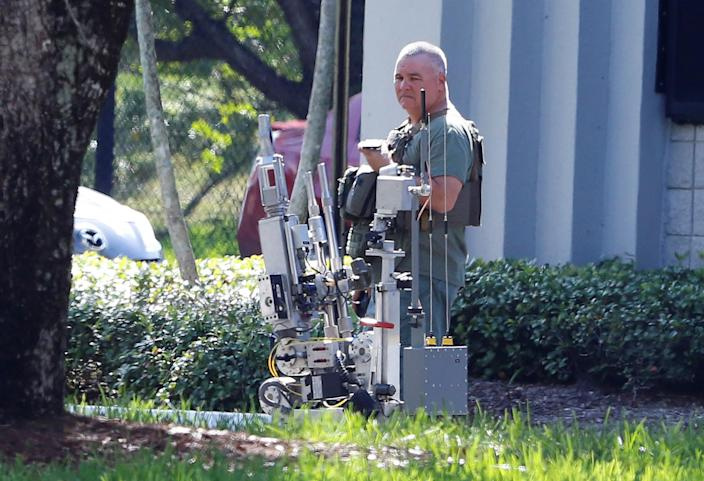 <p>Broward County Sheriff's Office bomb squad officer operates a robot outside a building containing the office of Rep. Debbie Wasserman Schultz as the Broward County Sheriff's Office bomb squad performs a search in Sunrise, Fla., Oct. 24, 2018 (Photo: Joe Skipper/Reuters) </p>
