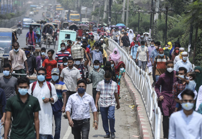People wearing face masks a precaution against the coronavirus leave the city to travel to their native places ahead of Eid al-Fitr in Dhaka, Bangladesh, Friday, May 7, 2021. India's surge in coronavirus cases is having a dangerous effect on neighboring Bangladesh. Health experts warn of imminent vaccine shortages just as the country should be stepping up its vaccination drive, and as more contagious virus variants are beginning to be detected. (AP Photo/Mahmud Hossain Opu)