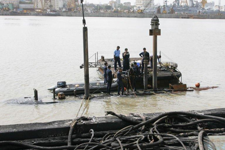 """Indian Navy divers inspect the conning tower of the stricken INS Sindhurakshak, after the submarine sank following an explosion at the naval dockyard in Mumbai, on August 14, 2013. Indian divers and engineers have struggled to refloat a submarine that exploded with 18 crewmen on board, as the prime minister voiced """"deep regret"""" at the blast which is feared to have left no survivors"""