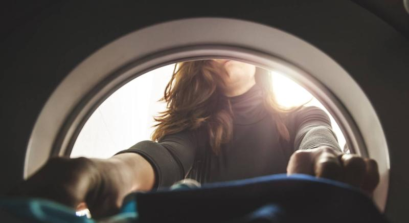 Woman puts laundry into the washing machine [Photo: Getty]