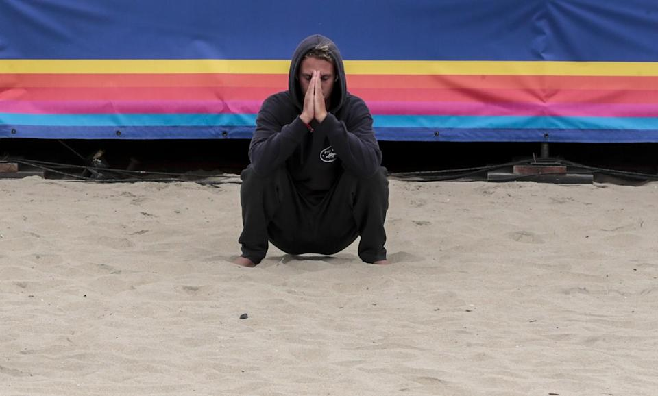 Surfer Jake Marshall stretches and meditates moments before competing in the finals