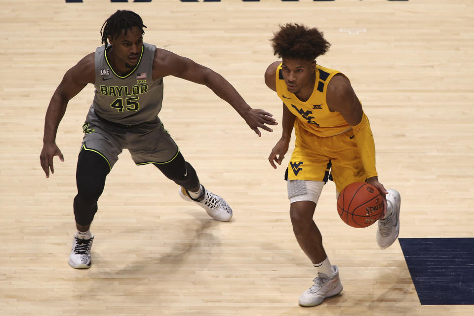 West Virginia guard Miles McBride (4) is defended by Baylor guard Davion Mitchell (45) during the first half of an NCAA college basketball game Tuesday, March 2, 2021, in Morgantown, W.Va. (AP Photo/Kathleen Batten)