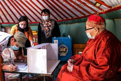 Electoral staff collect the vote of an elderly Mongolian at his home because the man cannot visit a polling station