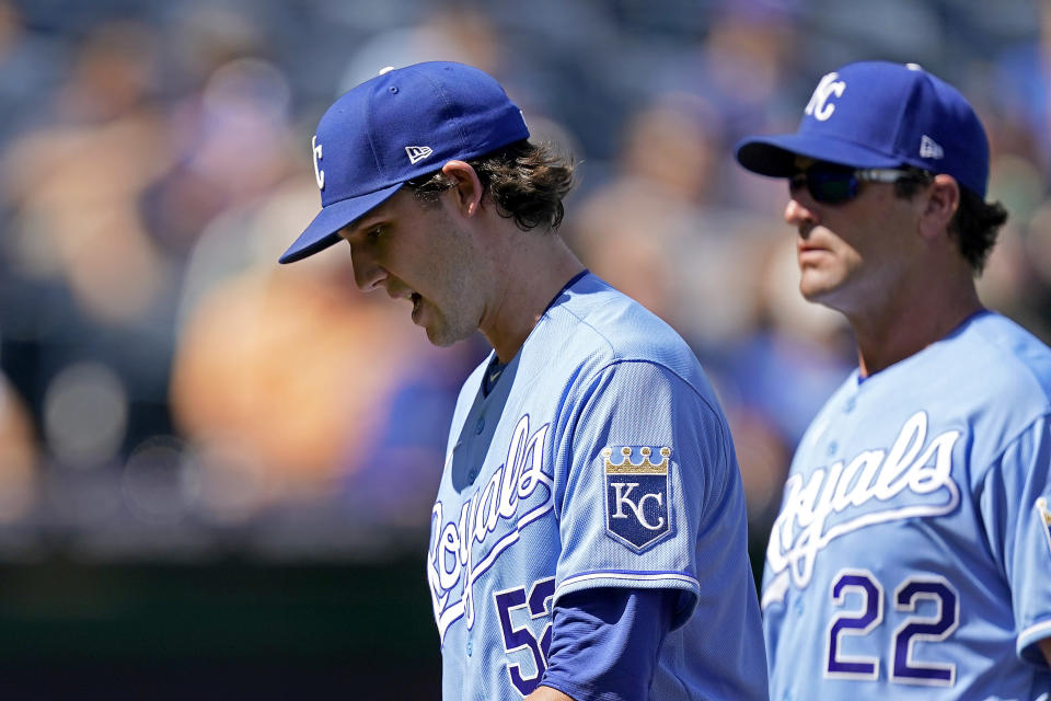 Kansas City Royals starting pitcher Daniel Lynch is followed to the dugout by Mike Matheny (22) as he comes out of the game during the third inning of a baseball game Thursday, Sept. 16, 2021, in Kansas City, Mo. (AP Photo/Charlie Riedel)