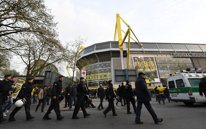 Police officers and fans stand in front of the Signal Iduna Park in Dortmund, Germany - AP