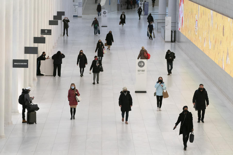 Commuters practice social distancing as they walk through a corridor at the World Trade Center, Thursday, March 4, 2021, in New York. A year after the pandemic began, the nation's largest metropolis is adapting and showing new life. (AP Photo/Mark Lennihan)