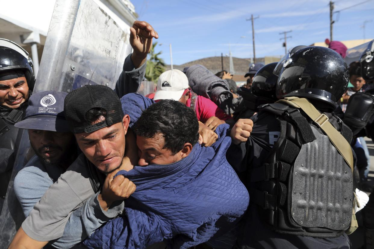 Migrants clash with Mexican police at the Mexico-U.S. border after getting past another line of Mexican police at the Chaparral crossing in Tijuana, Mexico, Sunday, as they try to reach the U.S. (Photo: Rodrigo Abd/AP)