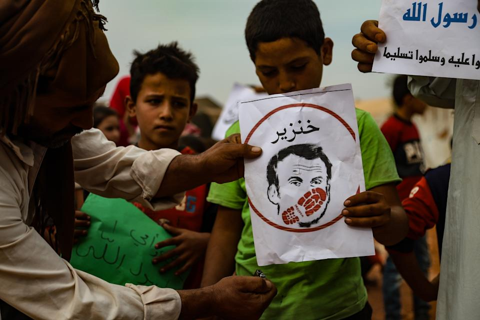IDLIB, SYRIA - OCTOBER 25: Citizens, holding banners, gather to stage a demonstration to protest against French President Emmanuel Macronâs statements of Islam and Muslims, on October 25, 2020 in Idlib, Syria. (Photo by Muhammed Abdullah/Anadolu Agency via Getty Images)
