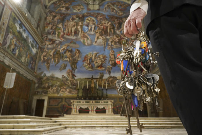 """Gianni Crea, the Vatican Museums chief """"Clavigero"""" key-keeper, walks through the Sixtine Chapel as he opens the museum, at the Vatican, Monday, Feb. 1, 2021. Crea is the """"clavigero"""" of the Vatican Museums, the chief key-keeper whose job begins each morning at 5 a.m., opening the doors and turning on the lights through 7 kilometers of one of the world's greatest collections of art and antiquities. The Associated Press followed Crea on his rounds the first day the museum reopened to the public, joining him in the underground """"bunker"""" where the 2,797 keys to the Vatican treasures are kept in wall safes overnight. (AP Photo/Andrew Medichini)"""