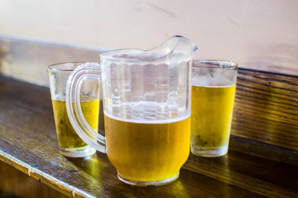 Beer poured into two cold glasses next to a pitcher.