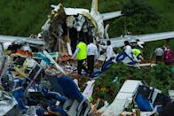 Officials inspect the wreckage of an Air India Express jet at Calicut International Airport in Karipur, Kerala, on August 8, 2020. - Fierce rain and winds lashed a plane carrying 190 people before it crash-landed and tore in two at an airport in southern India, killing at least 18 people and injuring scores more, officials said on August 8. (Photo by Arunchandra BOSE / AFP) (Photo by ARUNCHANDRA BOSE/AFP via Getty Images)