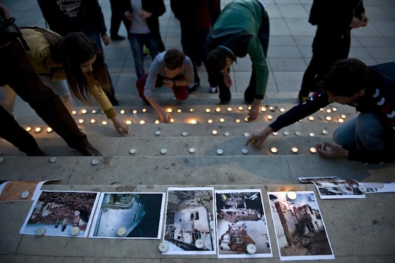 Albanians light candles and show pictures of the destruction of Kumanovo, in Pristina, on May 12, 2015 (AFP Photo/Armend Nimani)
