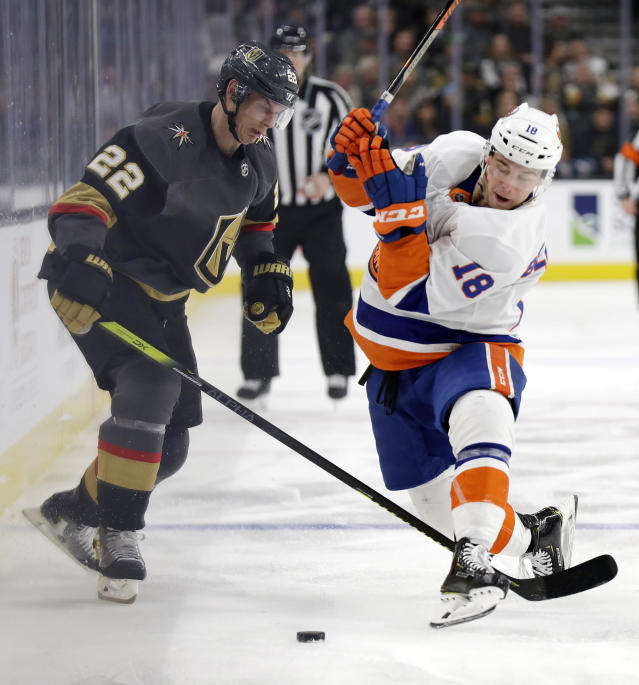 Vegas Golden Knights defenseman Nick Holden (22) and New York Islanders forward Anthony Beauvillier (18) become entangled during the first period of an NHL hockey game Saturday, Feb. 15, 2020, in Las Vegas. (AP Photo/Isaac Brekken)