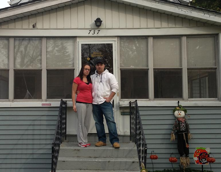 In this Oct. 29, 2013 photo, Teresa and Dan Reynolds stand in front of their Niagara Falls, N.Y., house in the neighborhood once known as Love Canal. Thirty-five years after Love Canal's oozing toxic waste forced the abandonment of the area, a new generation of residents, including the Reynolds, say history could be repeating itself. They are suing, claiming seeping chemical waste has contaminated their home and is making them ill. (AP Photo/Carolyn Thompson)