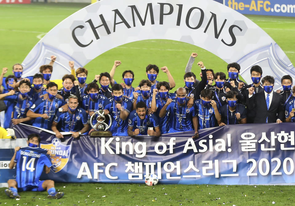 FILE - In this Dec. 19, 2020, file photo, Ulsan Hyundai's players celebrate with their trophy after the AFC Champions League final match against Persepolis in Al Wakrah, Qatar. The Asian Champions League's eastern zone competition will finally kick off after a series of delays and withdrawals. But the troubled tournament has a different look to previous editions of the continental club championship. (AP Photo/Hussein Sayed, File)