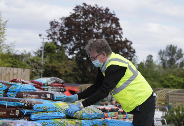Boyd Douglas-Davies, Communications Director for British Garden Centres, lifts compost bags at Osterley Garden Centre in London as the country is in lockdown to help stop the spread of coronavirus, Wednesday, May 13, 2020. Some of the coronavirus lockdown measures are being relaxed in England on Wednesday, with garden centres reopening but with extra measures such as social distancing. (AP Photo/Kirsty Wigglesworth)