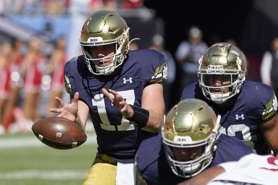 Notre Dame quarterback Jack Coan takes a snap from center in the shotgun formation during the first half of an NCAA college football game against Wisconsin Saturday, Sept. 25, 2021, in Chicago. (AP Photo/Charles Rex Arbogast)