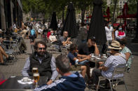 FILE - In this May 28, 2021, file photo, customers sit in a terrace bar in downtown Barcelona, Spain. Coronavirus infections, hospitalizations and deaths are plummeting across much of Europe. Vaccination rates are accelerating, and with them, the promise of summer vacations. (AP Photo/Emilio Morenatti, File)