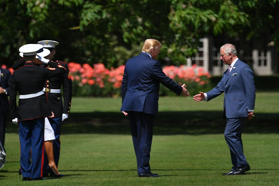Prince Charles, the Prince of Wales, greets President Trump as he touches down at Buckingham Palace on Monday. (MANDEL NGAN/AFP/Getty Images)