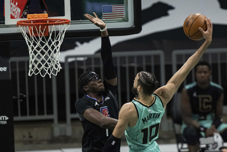 Charlotte Hornets forward Caleb Martin (10) tries to dunk the ball while guarded by Los Angeles Clippers guard Reggie Jackson (1) during the first half of an NBA basketball game in Charlotte, N.C., Thursday, May 13, 2021. (AP Photo/Jacob Kupferman)