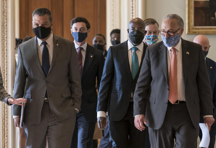 On the first full day of the Democratic majority in the Senate, new members walk to a news conference with Senate Majority Leader Chuck Schumer, D-N.Y., front right, at the Capitol in Washington, Thursday, Jan. 21, 2021. From left are, Sen. Alex Padilla, D-Calif., who took the seat vacated by Vice President Kamala Harris, Sen. Jon Ossoff, D-Ga., Sen. Raphael Warnock, D-Ga., Sen. John Hickenlooper, D-Colo., Sen. Chuck Schumer, D-N.Y., and Sen. Mark Kelly, D-Ariz. (AP Photo/J. Scott Applewhite)